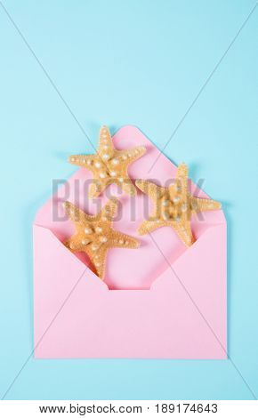 Pink Envelope With Three Starfishes On Colored Mint Blue Background