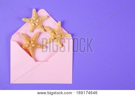 Pink Envelope With Three Starfishes On Colored Purple Background