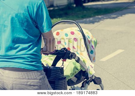 Closeup of mother hands pushing baby stroller. Protecting newborn from direct sunlight with a towel.
