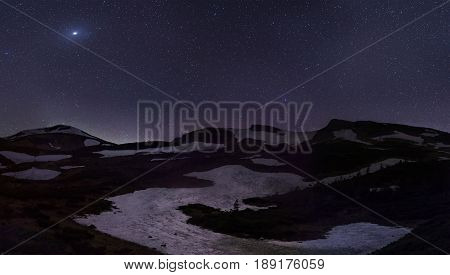 stars over snowy hills in the mountains
