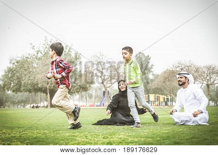 Arabic family playing with kids in a park
