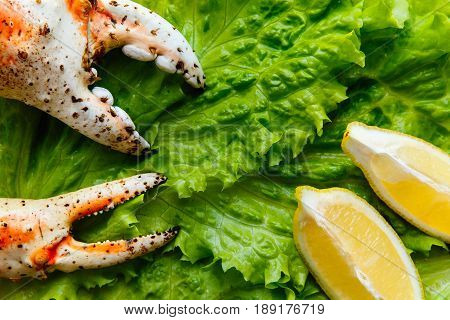 Far Eastern boiled crab claws lie on a cutting board on a sheet of green salad with lemon wedges. The concept of seafood in Russia and the Kola Peninsula and Kamchatka. Background, texture.