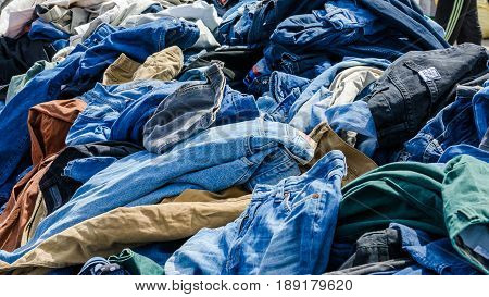 Heaps of clothing on the second hand market. Pile of second hand clothes at a garage sales