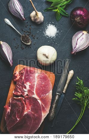 Raw Meat, Vegetables And Seasoning On Dark Concrete Background