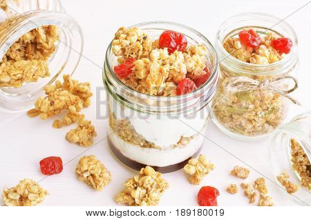 Greek natural yogurt with dry cherry and wholegrain granola in small jars against white background