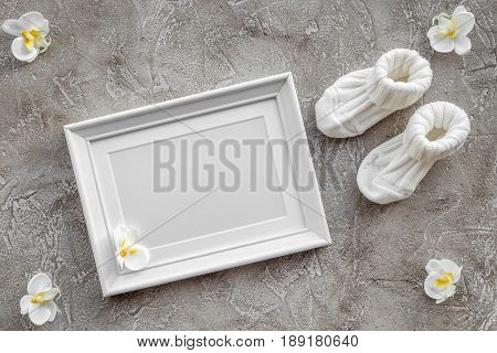 baby shoes and frame for baby shower design on gray stone background top view mock-up