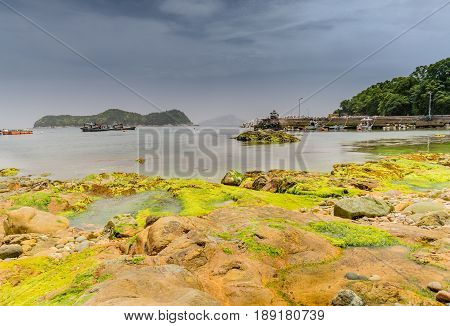 Seascape of a shoreline of large boulders covered with green algae with boats in the sea in front of an island and a pier in the right frame