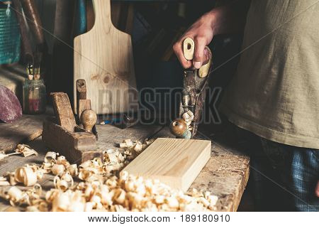 Carpenter with a planer at work in the workshop