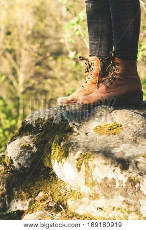 Female legs shod in Hiking boots on the forest background. Travel concept
