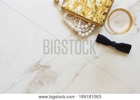 Glamorous gold sequined purse with pearls spilling out, black bow tie and cocktail glass with champagne. White marble copy space.