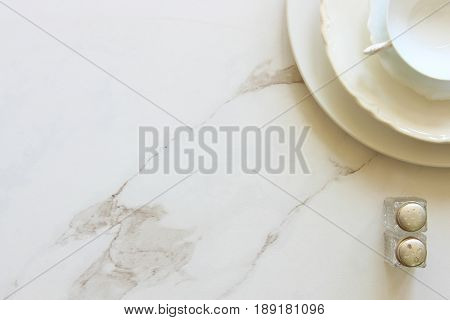 Simple white monochromatic table setting. White marble copy space.