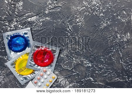 male contraception for safe sex with condoms on dark desk background top view mock up