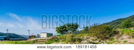 Panoramic view of rocky ground with bushes and a few trees and buildings under a blue sky with a thin layer of clouds.