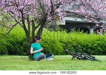 Beautiful girl bicyclist is resting with a phone under a flowering tree background