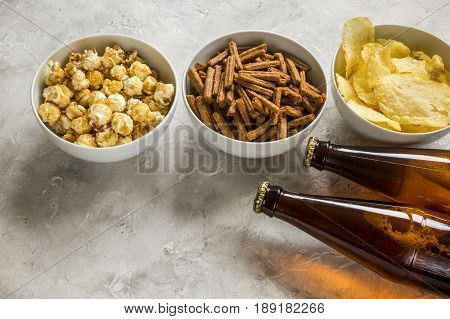 watching TV set with beer, chips, pop corn and crumbs on stone table background