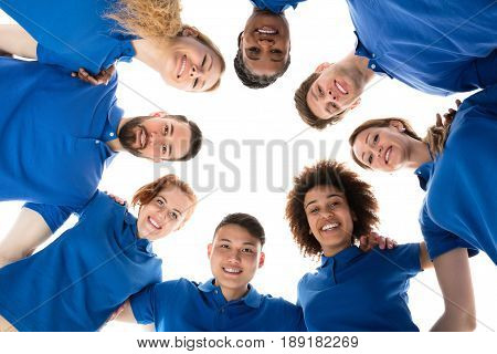 Low Angle View Of Happy Multiracial Janitors Forming Huddle