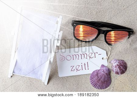 Sunny Summer Label With German Text Sommerzeit Means Summertime. Flat Lay View. Summer Decoration With Deck Chair, Seashells And Sunglasses. Greeting Crad With Sand Background