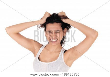 A very upset young Hispanic woman with her eyes closed messing her hair with both hands isolated for white background.