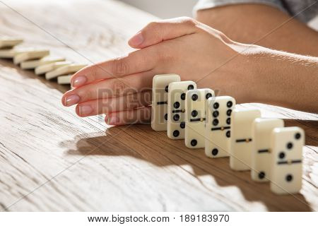 Close-up Of A Businesswoman Stopping Domino From Falling On Wooden Desk
