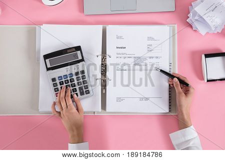 Close-up Of A Businesswoman Using Calculator While Calculating Invoice On Pink Desk