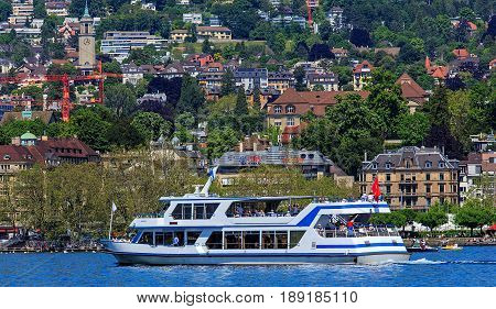 Zurich, Switzerland - 26 May, 2016: people in boats on Lake Zurich, city of Zurich in the background. Lake Zurich is a lake in Switzerland, extending southeast of the city of Zurich, which is the largest city in Switzerland.