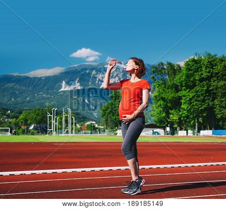 Beautiful pregnant sporty fitness woman on red running track field. Concept of training workout exercising at summer outdoors on sport stadium. Sport healthy lifestyle while pregnancy.