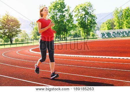 Pregnant sporty fitness woman jogging on red running track in stadium. Training summer outdoors on running track line with mountains on background. Sport healthy lifestyle while pregnancy concept.
