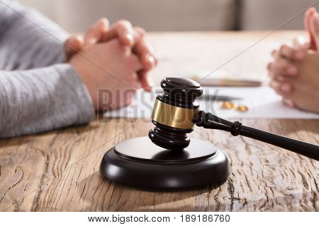 Gavel In Front Of Couple's Hand On Wooden Table