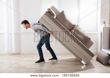 Young Man Trying To Move Sofa At Home