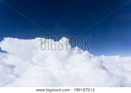 Deep blue sky above white fluffy cloud formation sky high.