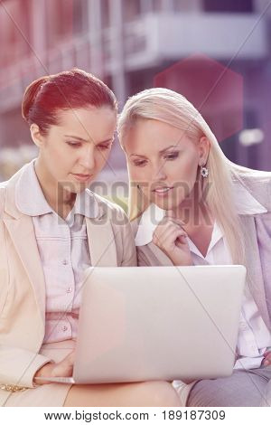 Young businesswomen working on laptop together while sitting outdoors