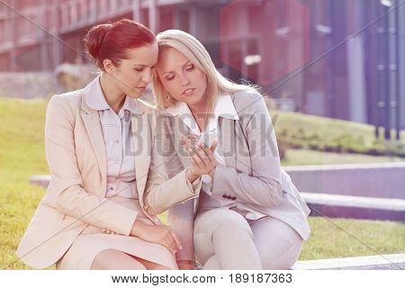 Young businesswomen using mobile phone together while sitting against office building
