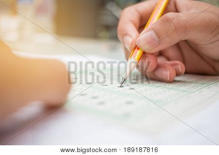 blurred of Asian Thai student testing in exercise or taking exams answer sheets in school class room