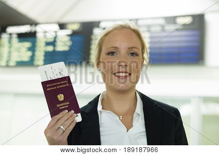 woman with passport and airline tickets at an airport waiting for their flight to the holiday.
