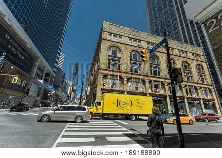 Toronto, Ontario, Canada, down town, May 20, 2017, great gorgeous wide open view of Toronto young street with fragment of old and modern buildings, walking people and various trucks in background