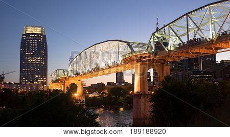 Night falls as pedestrians walk across a bridge for an event