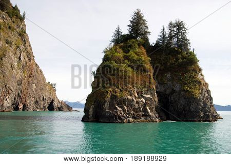 Beautiful rock buttes jut out of the ocean growing vegetation