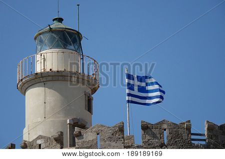 Low angle view of a lighthouse with a Greek flag