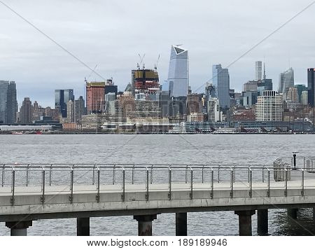 NEW YORK, NY - APR 1: View of Manhattan, from Hoboken, New Jersey, as seen on April 1, 2017. New York is the largest city by population in the USA and has millions of yearly visitors.