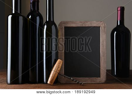 A wine menu chalk board with bottles of wine and cork screw. On a rustic wood table with light to dark grey background.