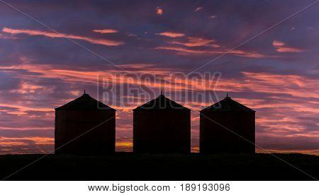 three grain bins under an evening sky