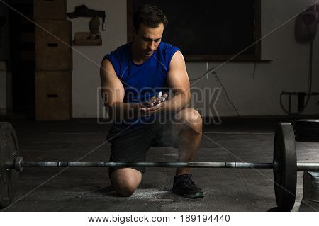 Athletic Man Using Gym Chalk
