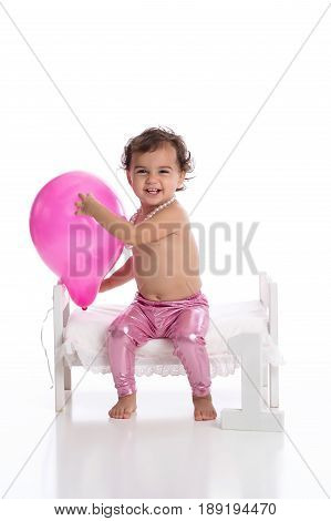 A laughing one year old baby girl holding a pink balloon. She is wearing metallic pink leggings a string of pearls and sitting on a tiny bed on a white seamless background.