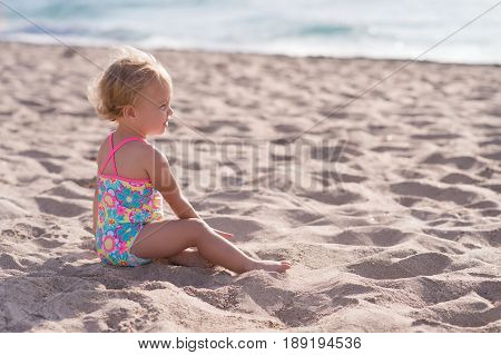 Side profile of a one year old baby girl sitting on a sandy beach.