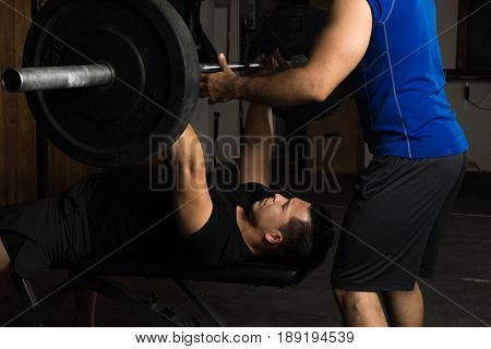 Good looking young man doing bench presses while getting help from his personal trainer and spotter