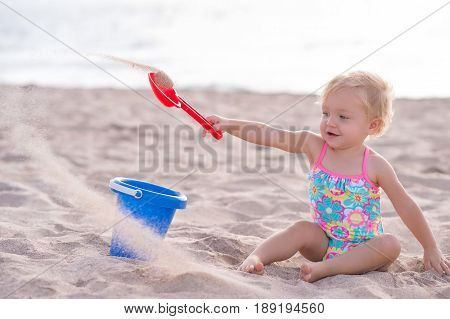 A one year old baby girl playing with a shovel and bucket in the sand. Shot outdoors on a sandy beach.