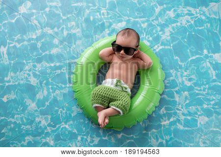 Two week old newborn baby boy sleeping on a tiny green inflatable swim ring. He is wearing green crocheted board shorts and black sunglasses.