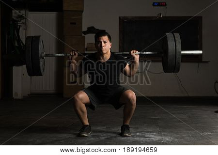 Strong Man Lifting A Barbell At The Gym