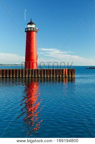The bright red Pierhead Lighthouse at Kenosha Wisconsin is reflected in early morning light on the waters of Lake Michigan.
