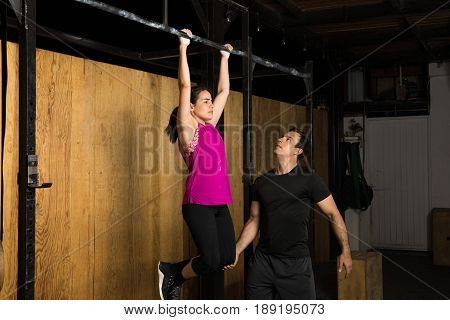 Male Trainer Helping A Woman At The Gym